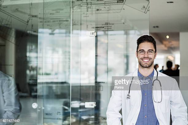 Portrait of happy male doctor standing in clinic