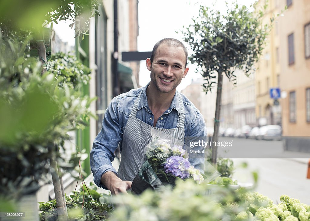 Portrait of happy male florist working outside flower shop