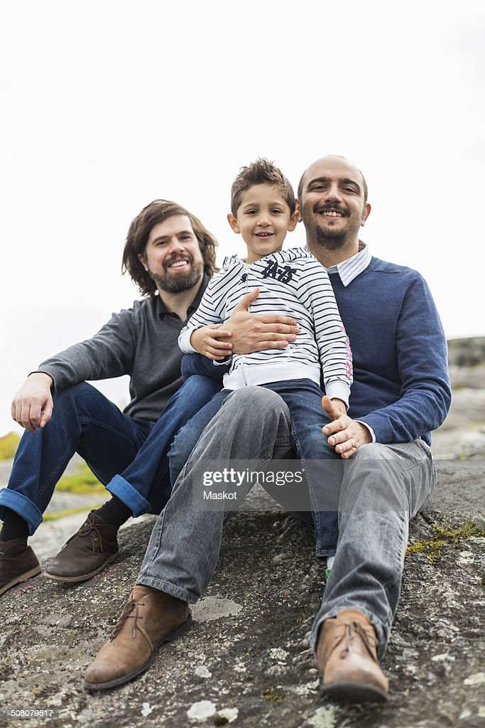 Portrait of happy male homosexual family relaxing on rock