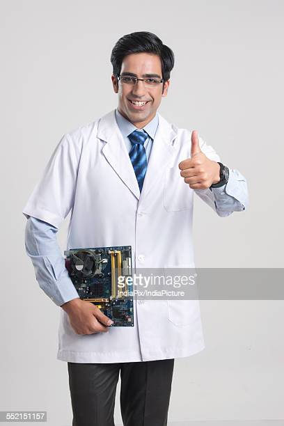 Portrait of happy male technician gesturing thumbs up while holding mother board over gray background