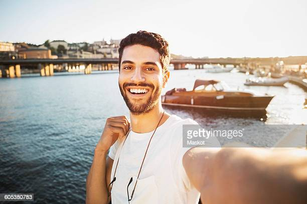 Portrait of happy male tourist by river in city