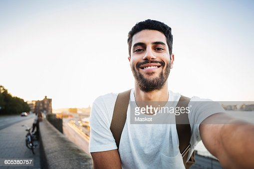 Portrait of happy male tourist sitting on retaining wall of bridge