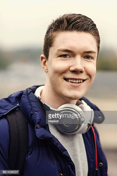 Portrait of happy male university student with headphones around neck outdoors