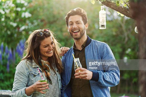 Portrait of happy man enjoying with woman while holding drink bottles at summer party