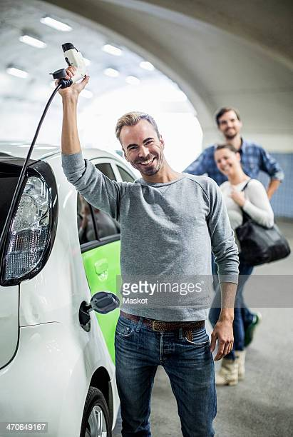 Portrait of happy man holding electrical charger with friends standing in background at gas station