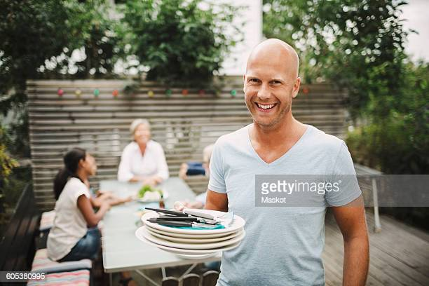 Portrait of happy man holding plates with family sitting at outdoor table in yard