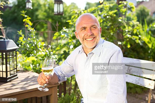 Portrait of happy man sitting with glass of white wine relaxing in the garden