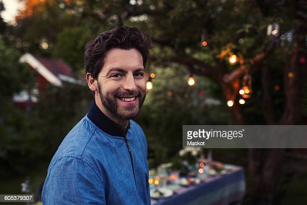 Portrait of happy man standing by dinner table at yard