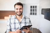 Close-up portrait of happy man using digital tablet in kitchen