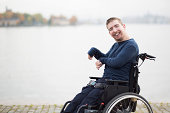 Portrait of happy man with cerebral palsy sitting on wheelchair by lake