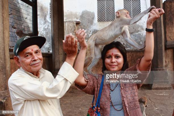 Portrait Of Happy Man With Daughter Holding Monkey