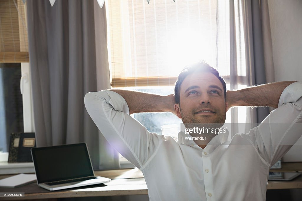 Portrait of happy man with hands behind his head at his home office