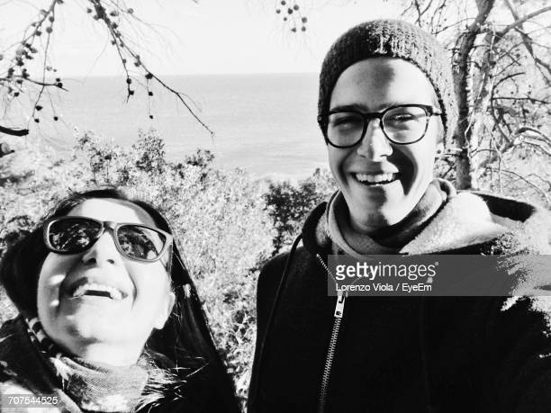 Portrait Of Happy Man With Mother In Forest Against Clear Sky