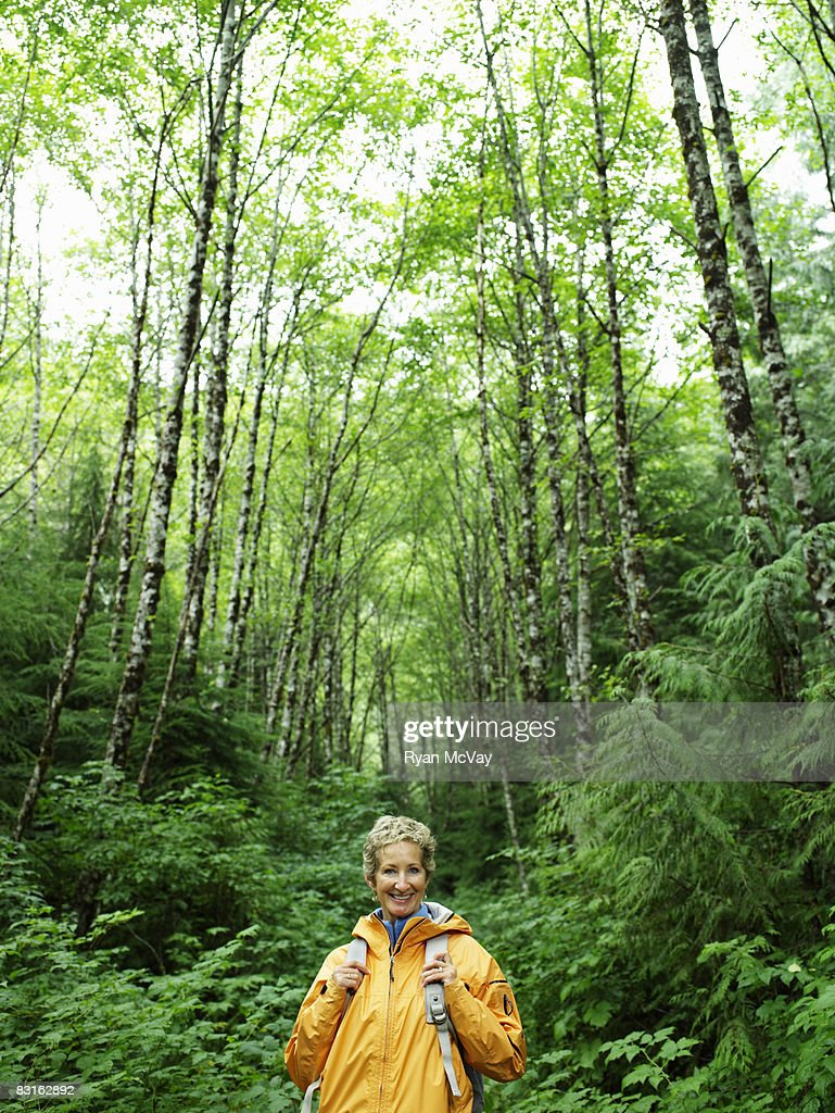 Portrait of happy mature woman in forest. : Stock Photo