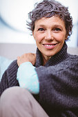 Portrait of happy mature woman sitting on sofa at home