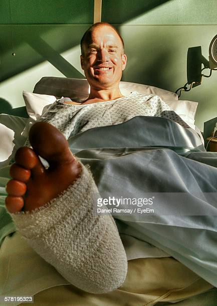 Portrait Of Happy Mid Adult Man With Broken Leg Recovering In Hospital Bed