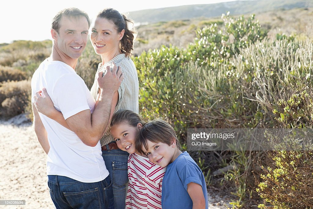 Portrait of happy mid couple enjoying vacations with kids : Stock Photo