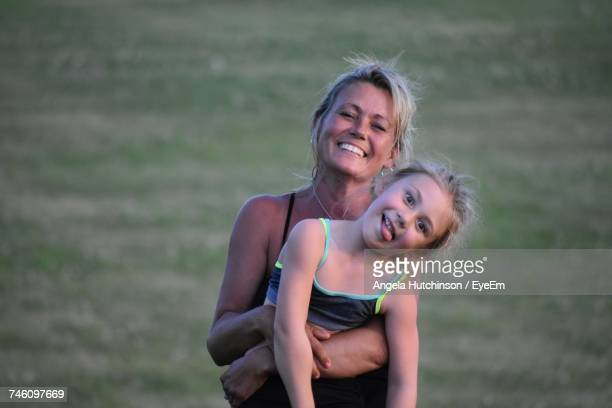 Portrait Of Happy Mother Carrying Daughter While Standing On Field