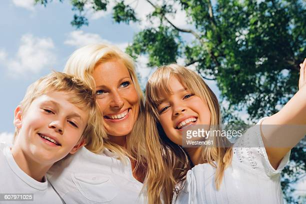 Portrait of happy mother with her children in nature