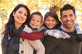Portrait of happy parents piggybacking kids outdoors