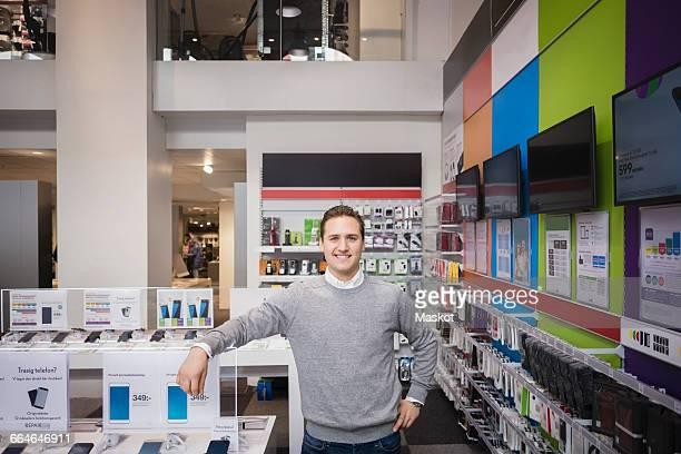 Portrait of happy salesman standing in store