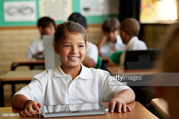Portrait of happy schoolgirl in classroom