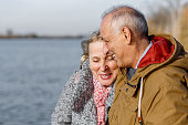 Portrait of happy senior couple embracing by the lake on sunny autumn day.
