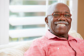 Portrait Of Happy Senior Man At Home Looking At Camera Smiling