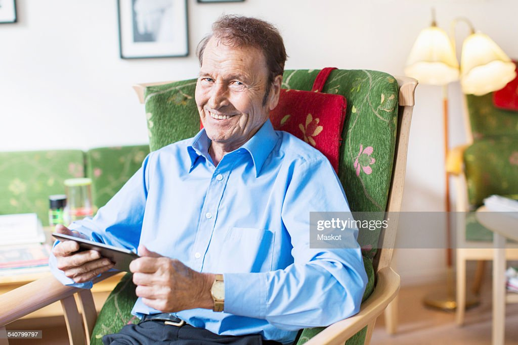 Portrait of happy senior man holding digital tablet while sitting on armchair at nursing home