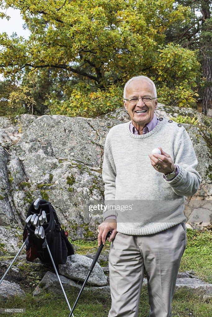 Portrait of happy senior man holding golf ball and club in yard