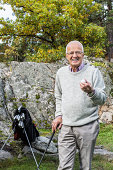 Portrait of happy senior man holding golf ball and club in yard