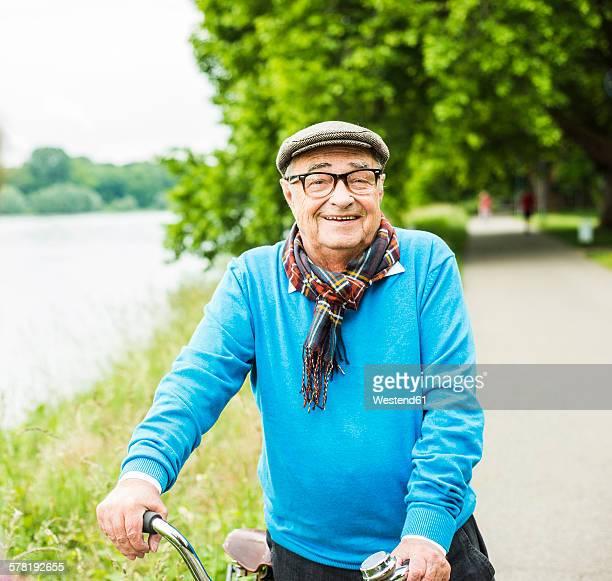 Portrait of happy senior man on his bicycle