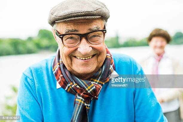 Portrait of happy senior man with glasses and cap