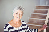 Portrait of happy senior woman against staircase at home