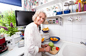 Portrait of happy senior woman chopping fresh vegetables at kitchen counter
