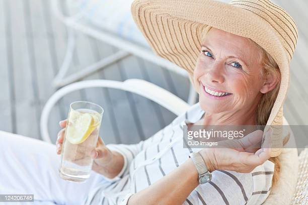 Portrait of happy senior woman having a glass of lemonade