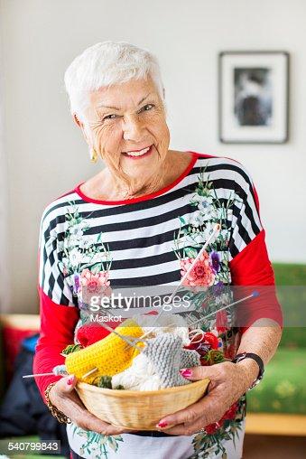 Portrait of happy senior woman holding knitting basket at nursing home