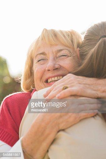 Portrait of happy senior woman hugging ger granddaughter