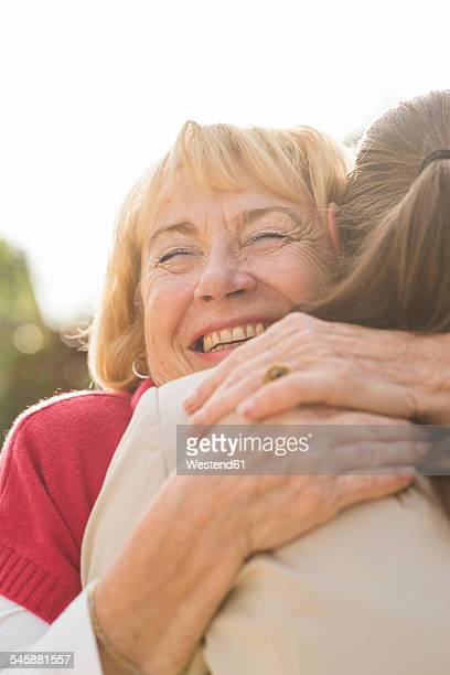 Portrait of happy senior woman hugging ger granddaughter