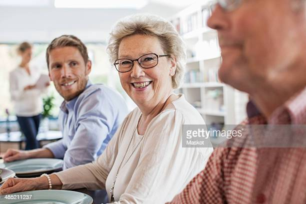 Portrait of happy senior woman sitting with family at dining table