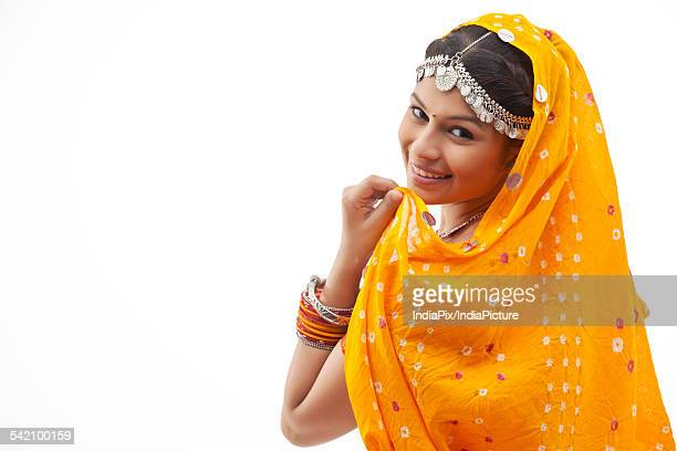 Portrait of happy shy woman in traditional clothing looking over shoulder against white background