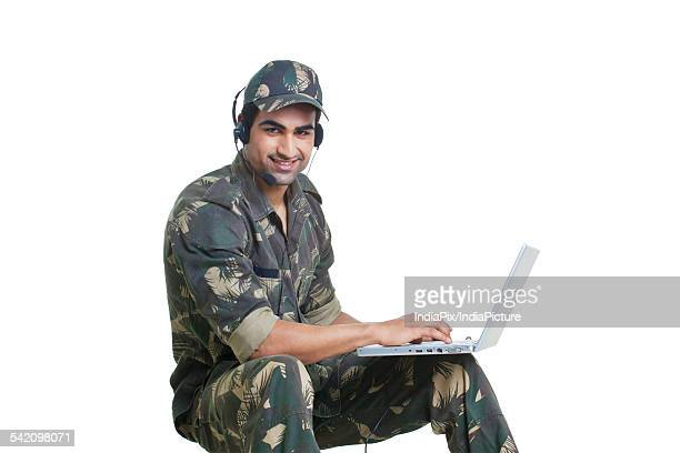 Portrait of happy soldier chatting on laptop