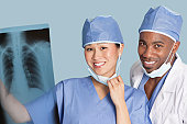 Portrait of happy surgeons holding x-ray report over light blue background