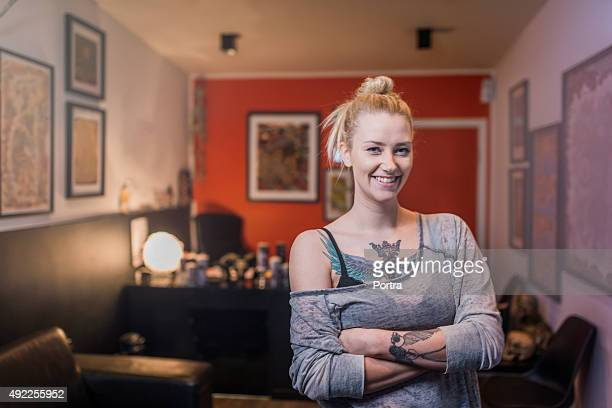 Portrait of happy tattooed woman in studio