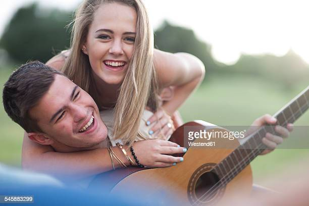 Portrait of happy teenage couple with guitar