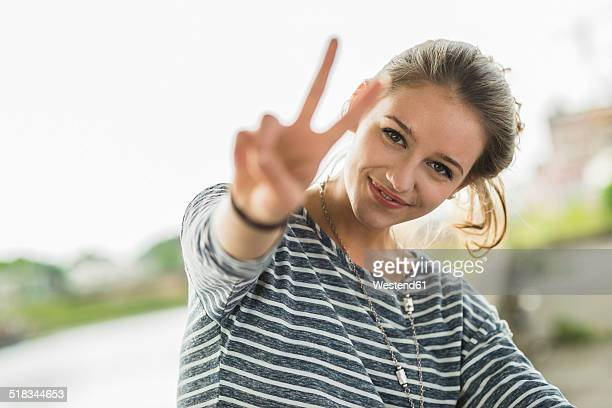 Portrait of happy teenage girl showing Victory sign