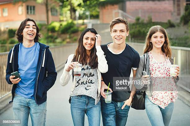 Portrait of happy teenagers holding disposable glasses and smart phones on bridge