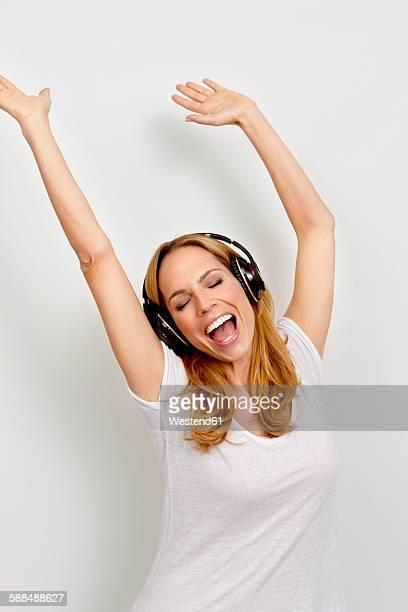 Portrait of happy woman enjoying listening to music on headphones