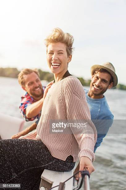 Portrait of happy woman enjoying with friends on yacht