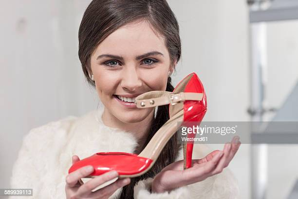 Portrait of happy woman holding new shoe